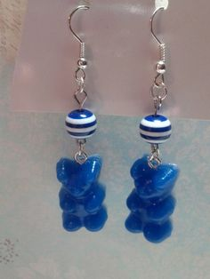 These adorable earrings are handmade by me. They each feature a blue gummy bear and a round blue and white striped bead.
