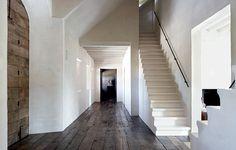 Grote hal met donkere houten vloer.