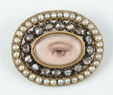 Circa 1820 Eye miniature brooch surrounded by diamonds set in black enamel and with a split pearl border.