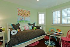 A brightly colored confetti print against a dark background on the bedding in this transitional kid's bedroom repeats the patterns on the vibrant area rug. Light green walls keep the room feeling playful and young. Bright pink and blue chairs echo the fun rug colors and provide extra seating for activities.