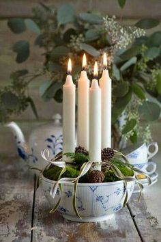 Beautiful....Advent candles arranged in a bowl with cones and ribbon.