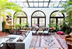Eclectic home solarium with layered rugs and indoor plants