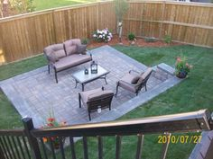 Formal manufactured brick patio recessed into a slope in a small backyard. Balanced planting beds in each corner of the yard compliment this simple, but effective design. Picture compliments of Dream-yard.