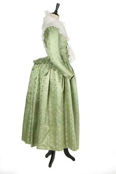 A rare brocaded satin pregnancy robe, 1790s. the pale green silk sprigged overall with ivory and peach trefoils tied with tassels, comprising: petticoat with waist ties and two matching bodices, one high fashion (for early pregnancy) in 'pierrot' style cut low and tight with closed front, faux waistcoat panels, short tails to the back lined in striped silk, narrow curved sleeves; the other in open-robe form with inner boned closed front panels and loose deshabillé-like outer panels, the…