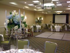 tall candelabras with flower arrangement on top made of blue and white flowers