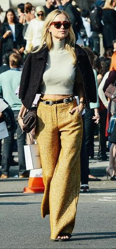 Pernille Teisbaek wears a cropped turtleneck sweater, belted wide-leg trousers, black cropped jacket, and tortoiseshell sunglasses