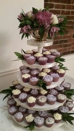 Purple and ivory flower themed cupcake tower with floral arrangement on top.