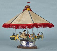 "Althof Bergmann tin clockwork carousel with six painted gondolas and horses with riders, 18 1/2"" h., 20"" dia."