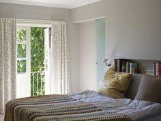 LUFTIG SONE: Døren leder ut til en liten balkong. De store trærne skaper skygge og variasjon inn i foreldresoverommet. Veggen bak sengen med innfelt oppbevaringsnisje er ny. Bak den er detblitt plass til et nytt bad og en stor walk-in-garderobe. Veggene er malt ifargen Demring fra Jotun, fargekode NCS 2502-Y17R.