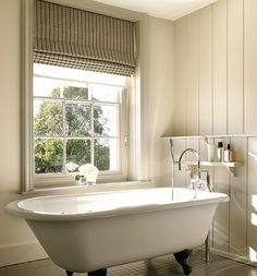 Georgian Farmhouse with a period bath and groove paneling on the walls. The blind adds touch of softness. I think I'd add a few more accessories in here though!  If you like this, why not head on over to http://www.TheHomeDesignSchool.com/signup  for more modern country design inspiration, plus get FREE access to our home design resource library.