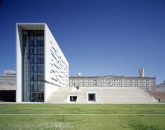 Rectory of Universidade Nova de Lisboa by AIRES MATEUS, Lisbon, Portugal - . Its façades are clad in white stone with an abstract layout of fenestration concealing the many levels of the building.