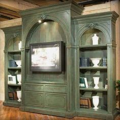 Unusual antique green built-in unit with bookcases -- and a murphy bed that folds up into the wall behind the TV!