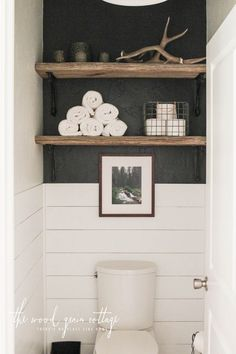 How to decorate shelves above toilet. White shiplap, black accent wall, rustic wooden floating shelves with metal brackets. #ad #bathroom #shiplap #farmhouse #fixerupper