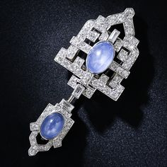 This enchanting and ingeniously engineered Art Deco jewel can be worn both as a single clip or as a double jabot pin. The geometrically designed clip highlights a beautiful denim blue oval star sapphire, weighing 5.00 carats, and sparkles with 1.50 carats of bright-white European-cut and single-cut diamonds. The smaller star sapphire at the end of the jabot weighs 2.00 carats