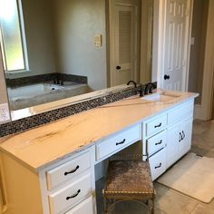 Cambria Britannica Gold installation by Winston Floors + Countertops in a master bathroom with tiled accent backsplash.
