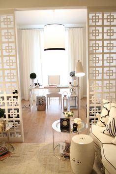 Creamy Office with white drum pendant and black trim, open trellis room divider and cream couch with black piping - Reception & Waiting Area of Ana Antunes Home-Styling Showroom