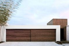 18 Inspirational Examples Of Modern Garage Doors // A sliding wood door made from the same wood used on the exterior helps the door blend in.