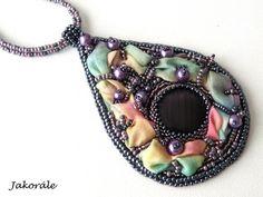 Jednoduchý a přitom nepřehlédnutelný náhrdelník zhotovený technikou korálkové výšivky s originál hedvábím. Použit je japonský rokajl TOHO, rokajl Preciosa, fialovým skleněným kabošonem a fialovými perličkami. Přívěsek je zavěšený na dvojitém návleku z korálků.  Náhrdelník je z rubu podšitý šedým filcem.  Rozměry přívěsku cca 9 x 6 cm. Délka náhrdelníku je 42,5 cm a je možné prodloužit až o 5 cm díky předanému prodlužovacímu řetízku.  Zapínání bižuterní - černé.