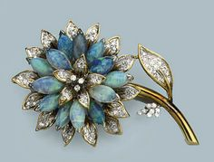 AN OPAL AND DIAMOND BROOCH   Composed as a flower set with navette shaped opals and enhanced with diamonds, circa 1970