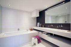 Badkamer in composietsteen van Q-artz. In deze badkamer is het Q-artz Custom Made concept compleet doorgevoerd. Maatwerk kwarts composietsteen is gebruikt voor de badombouw, douchewanden, achterwand wastafelopstelling en gehele vloer. De maatwerk wastafelopstelling is gebaseerd op de Q-artz Two serie. Q-artz