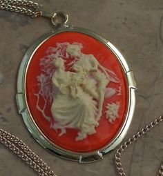 Lovers embrace cameo necklace. Olden day scene with a couple in love on a mock carnelian background. Large size pendant and chain from Susie Carol
