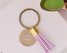 Alpha Gamma Delta Sorority Tassel Keychain Details  Tassels are so on-trend right now we had to find a way to incorporate them into our modern and minimalist sorority aesthetic! This Alpha Gamma Delta sorority keychain comes in your choice of color for a suede leather tassel and the brass charm is hand stamped by our team of sorority women in our workshop. Great gift for a sister, friend, or even for yourself! Each piece is handmade and unique! Buy for the holidays, Valentine's Day…