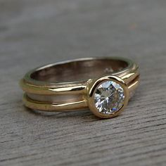 Now available with an ethical, lab-created diamond! Photos 1-4 show this ring with a 5mm moissanite; this listing is for the exact same design using diamond 1 shown in photo 5, which measures 4.8mm. (If youd like to view the lower-priced moissanite version, you can do so here - https://www.etsy.com/listing/252689725 ) Your diamond will be set in a 14k gold bezel on a 5mm wide layered 14k yellow gold and 18k palladium white gold band. 18k palladium white gold is a nickel-free alloy that…