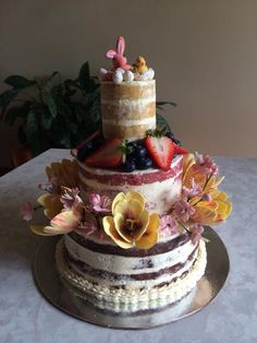 Naked Easter cake with a tiny gumpaste speckled eggs, bunny, chic, tulips and cherry blossoms. Chocolate, strawberry and almond white chocolate layers with vanilla Swiss meringue butter cream frosting.