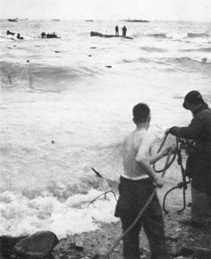 At Normandy Beach MEN FROM WRECKED LANDING CRAFT are being rescued by life lines carried out to them from the beach. Medical corps personnel performed many acts of heroism, working under fire to bring up the wounded men left on the tidal flat and threatened by rising tide.