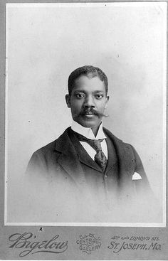 African American man seated, head and shoulders, in sack suit with wide silk tie and white shirt. c.1890