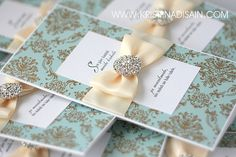 luxury wedding invitations with brooch and damask patterned designer paper
