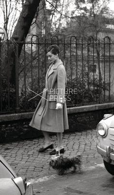 The actress Audrey Hepburn photographed with Mr. Famous by Elio Sorci in Rome (Italy), in October 1959. Audrey was wearing:Coat: Hermès (of beige wool, trench coat style, double-breasted with buttons of white resin, buttons also on the sleeves, detail of two pockets with flaps on the hips line in the front, at the waist a sash in the same tissue, length below the knees, liner of beige silk, of the collection for the Autumn/Winter 1957/58).Loafers: Gucci.