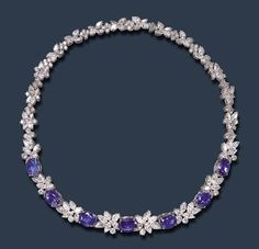 AN ELEGANT SAPPHIRE AND DIAMOND NECKLACE The flexible band, set at the front with a series of seven oval-cut sapphires, spaced by circular, pear and marquise-cut diamond foliate clusters, to the backchain of similarly-set cluster links alternating with circular-cut diamond quatrefoil links, mounted in platinum, 16¼ ins.