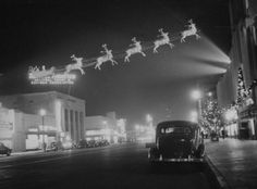 Santa and his reindeer fly over the Miracle Mile in this east-facing night view of Wilshire Boulevard at Burnside, 1930's. The El Rey Theater is visible on the left side of the street.