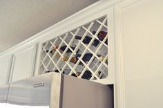 Install a wine rack lattice above the refrigerator.