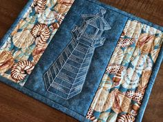 Mug rug with quilted central lighthouse and seashell print fabric on sides.
