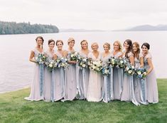 Bridesmaids in long blue grey cap sleeve Joanna August bridesmaid dresses with blue ribbon bouquets