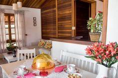 Divisórias de alvenaria formam banheiros, lavanderia e cozinha, cujo balcão em L também é de tijolos. O tampo de carvalho (nas larguras de 1,02 m e 0,85 m, com 23 cm de profundidade) acomoda refeições rápidas e faz as vezes de aparador em dias de festa. Próximo à meia-parede, está alocada a área de jantar. A mesa de seis lugares revela um convidado pouco comum: em meio às cadeiras, um banco oferece assento.