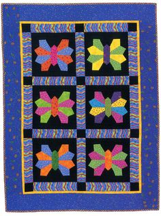 """Butterflies at Night from """"Bold, Black & Beautiful"""", AQS 2004. Dresden Plate blades for wings. Machine quilted onto black background squares."""