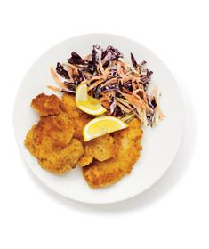 Crispy Chicken with Coleslaw:  1/3 cupsour cream  1tablespoon red wine vinegar  kosher salt and black pepper  1/2 small head red cabbage, thinly sliced (about 2 cups)  2 carrots, grated  8boneless, skinless chicken thighs (1 1/2 pounds)  1/2cup flour  2 eggs, beaten  1cupbread crumbs  1/2cupcanola oil  lemon wedges, for serving