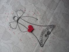 Anděl láskyplný červený... Anděl je udrátovaný z černého žíhaného drátu. V rukách drží velkéčervené srdce z keramické hmoty. Anděl je vysoký 33 cm a široký je 19 cm v křídlech. Srdíčko je veliké 5 cm x 5,5 cm Je ošetřen proti korozi.