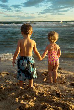 A little boy and a little girl walk on the beach