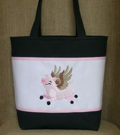 """This """"When Pigs Fly"""" embroidered tote is hand made in the USA from 100%  black and white cotton duck. The design was embroidered in shades of pink  and beige. Pink and white dotted swiss ribbon was used to separate the  colors and complete the look. The bag is fully lined in a coordinating pink  and white polka dots cotton. It measures 12"""" H x 10.5"""" W x 5"""" D. The straps measure 23"""" with a 11"""" drop.  Spot clean only.  This original bag would make a great gift for yourself or that special…"""