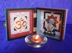 A tiny hindu shrine made in a box and illuminated with a tea light