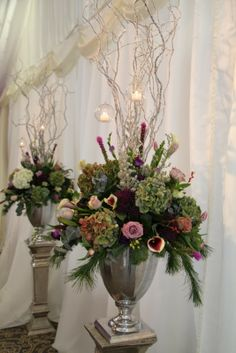 The two pedestal designs were topped with fresh flowers and foliages with candlelit orbs hanging from the branches