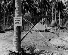 """Air raid warning gong photographed on Guadalcanal in November 1943. It was made from the nose cap of a Japanese 14"""" shell which fell on Henderson Field during a 1942 bombardment."""