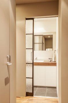明るい仕切り「型板ガラス」  サニタリーと廊下を仕切る、型板ガラスのアイアンサッシ。洗面所も白を基調として明るくスッキリと