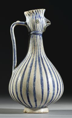 A KASHAN BIRD-HEADED EWER, PERSIA, 12TH/13TH CENTURY of elongated baluster form, with bulbous body narrowing to a neck with flaring mouth in the form of a chicken's head, the body decorated with underglaze cobalt blue stripes