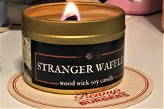 *new* STRANGER WAFFLES wood wick soy candle! Our customers asked for a tribute to Stranger Things, so we present to you this delicious buttery sweet waffle candle! Stranger Things Gifts, Eleven Stranger Things, Soy Candles, Candle Jars, Gifts For Bookworms, Container Size, Geek Gifts, Tin, Wicked