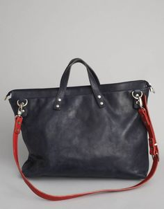 steve mono. black leather bag with red leather strap.